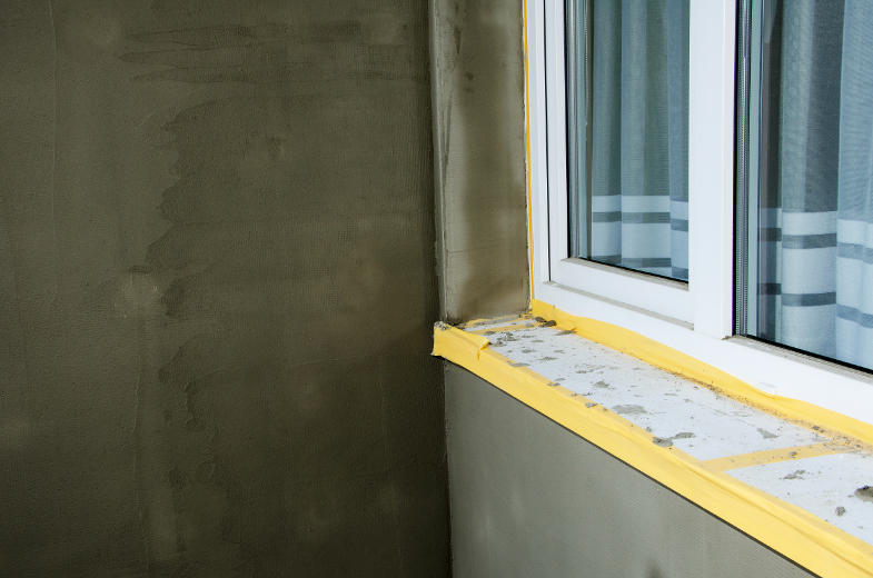 Semifinished repairing of balcony, gray plaster and dirty white window.